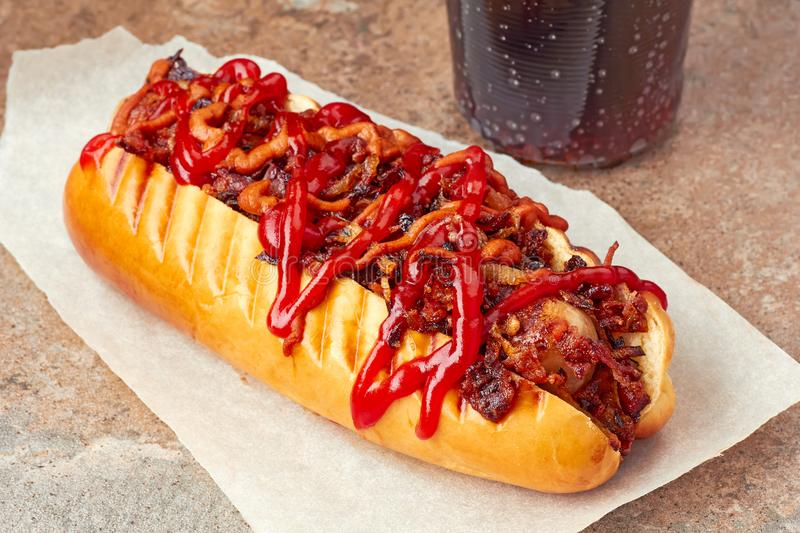 Tasty hot dog with sauces and toppings. On stone background royalty free stock photo