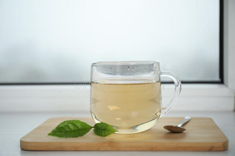 Tasty hot green tea in cup on window sill, closeup. Tasty hot green tea in cup on window sill stock photography