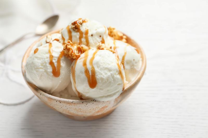 Tasty ice cream with caramel sauce and popcorn. In bowl on table stock images