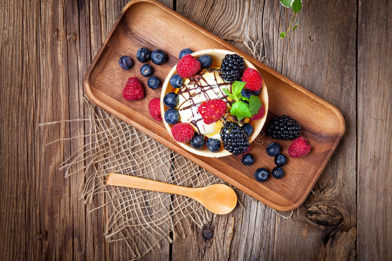 Tasty ice cream dessert with fruit in a waffle bowl. stock images