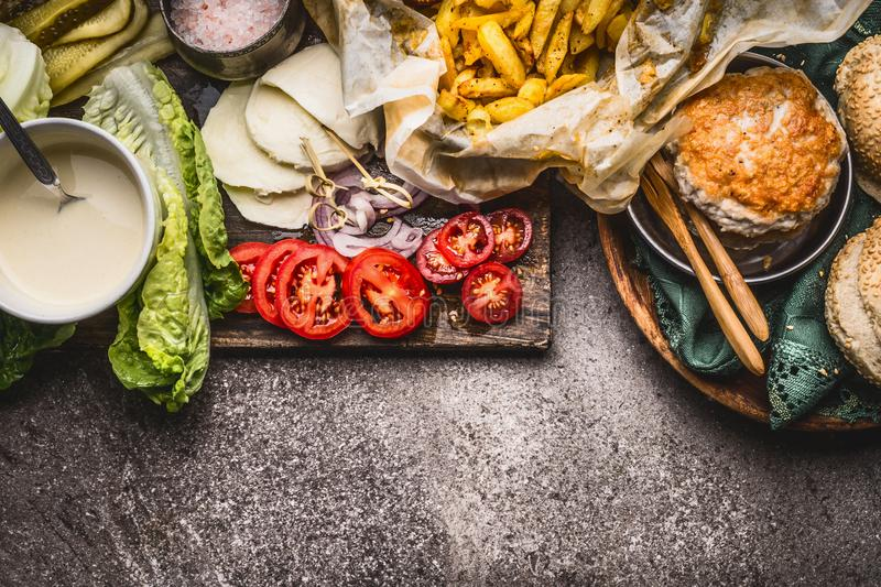 Tasty ingredients for chicken burger on rustic background , top view. Border royalty free stock image