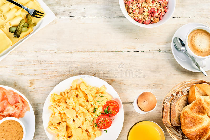 Tasty international breakfast food frame. With scrambled egg, ham, rolls and croissants, cereal, coffee and orange juice around central copy space on rustic royalty free stock photo