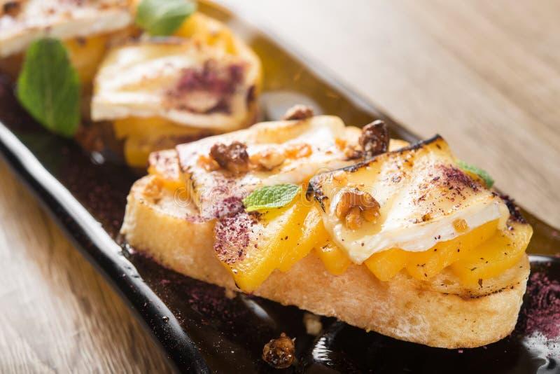 Italian bruschetta with cheese brie, camembert and peach. Tasty italian bruschetta with cheese brie, camembert and peach at a cafe table stock photo