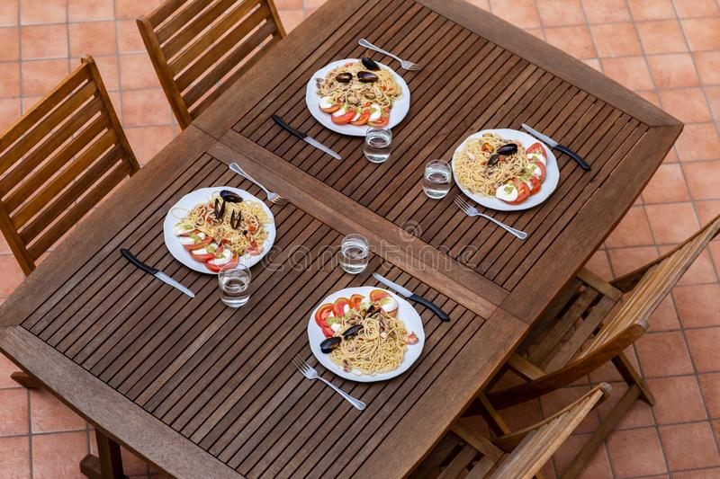 Tasty italian spaghetti pasta dinner with caprese salad on wooden table top view royalty free stock photo