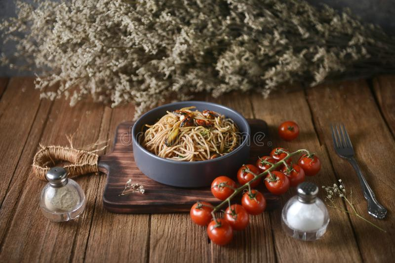 Tasty Italian spaghetti pasta with mussel, tomato and garnish on round dish and wooden plate for serving on wooden table stock photos
