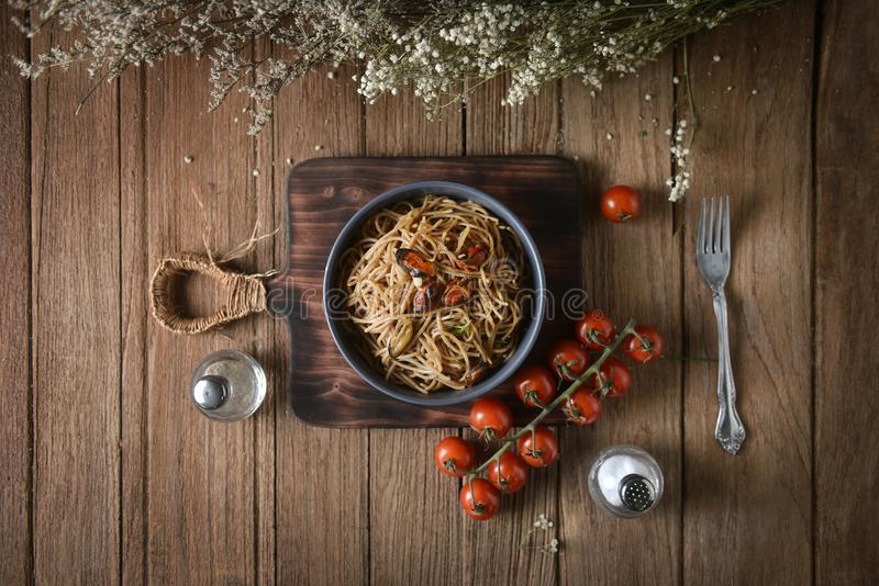 Tasty Italian spaghetti pasta with mussel, tomato and garnish on round dish and wooden plate royalty free stock photos