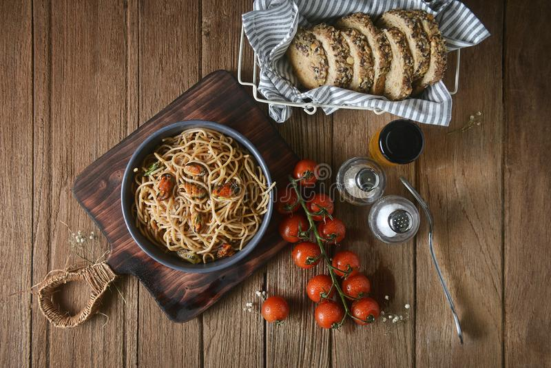 Tasty Italian spaghetti pasta with mussel, tomato, whole wheat bread and garnish on round dish and wooden plate for serving royalty free stock images