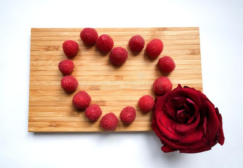 Tasty juicy ripe fresh red raspberry berries in the heart shaped form on a wooden cutting board and a red rose flowe royalty free stock photos