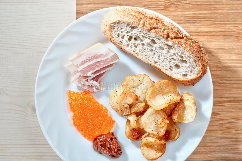 Tasty junk food. Greasy fried. Potatoes, bacon, red caviar, spicy sauce and white bread on a white plate. Russian snacking royalty free stock photos