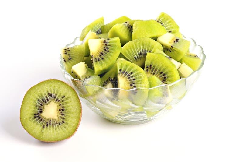 Tasty kiwi pieces in a bowl, half of kiwi, white background royalty free stock photo