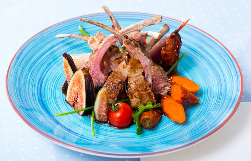 Tasty lamb ribs baked and served with vegetables and fresh figs. Image of  tasty lamb ribs baked and served with vegetables and fresh figs royalty free stock photos