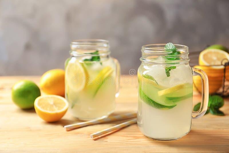 Tasty lemonade with mint in mason jars. On table stock photo