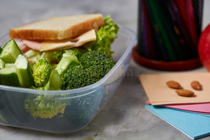 Tasty lunch with green lettuce and vegetables in container and school supplies, on white desk, selective focus. stock photos