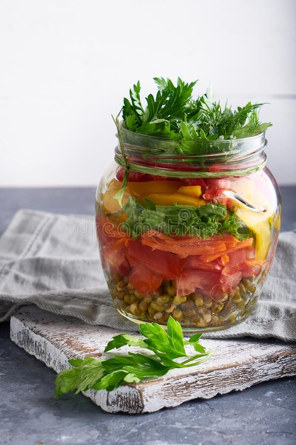 Tasty mason salad in jar. Homemade and healthy food Served on gray table royalty free stock images