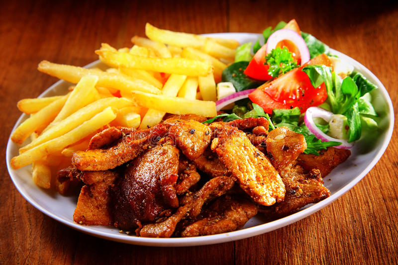 Tasty Meal Combination of Meat, Fries and Veggies. Close up Appetizing Healthy Meal Combination of Cooked Meat, French Fries and Fresh Veggies on Top of Brown stock photo
