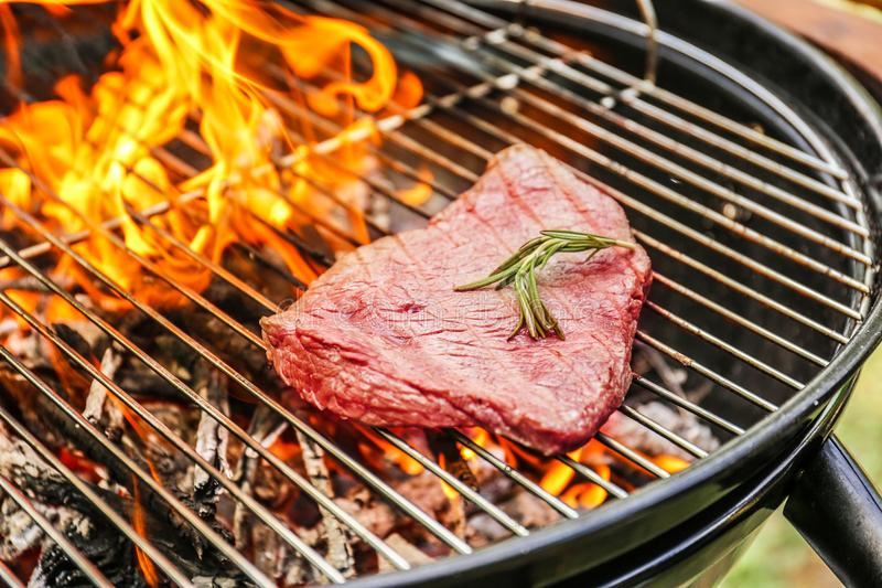 Tasty meat on barbecue grill with fire flames outdoors. Closeup stock photos
