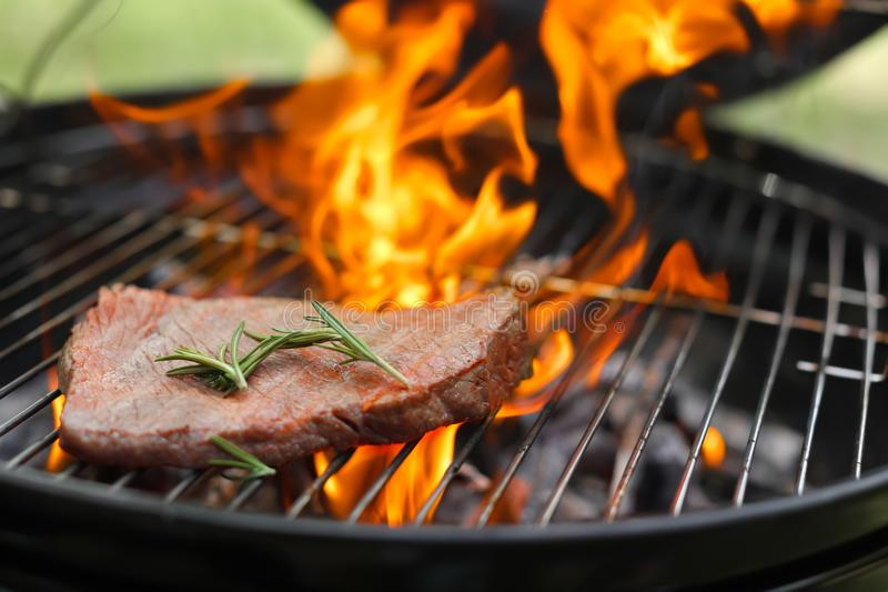 Tasty meat on barbecue grill with fire flames outdoors. Closeup stock photo