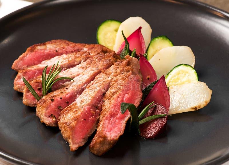 Tasty medium raw sliced roast beef with vegetables stock photos