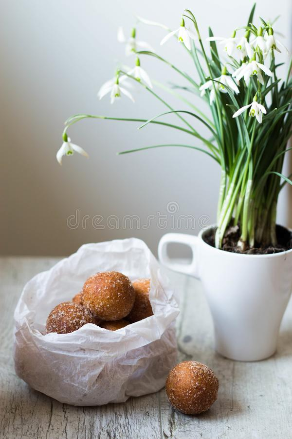Mini donuts in a paper bag and snowdrops flowers on a white, woode table stock images