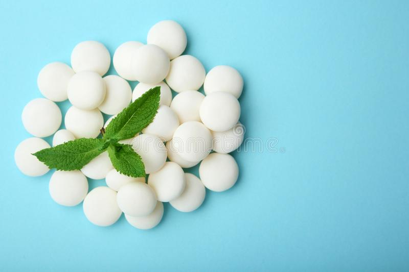 Tasty mint candies and leaves. On color background, top view royalty free stock image