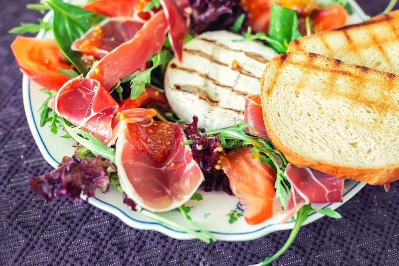 Tasty mixed salad dish with grilled camembert cheese, prosciutto ham, organic tomato and fresh green leaves. Healthy dilicious. Meal. Isolated on black royalty free stock images