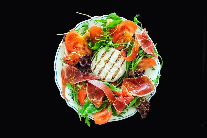 Tasty mixed salad dish with grilled camembert cheese, prosciutto ham, organic tomato and fresh green leaves. Healthy dilicious. Meal. Isolated on black. Flat stock image