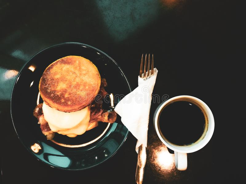 Tasty morning breakfast with omlette burger and cup of coffee. Roasted eggs with bakon and cheese on toasted bread. stock images