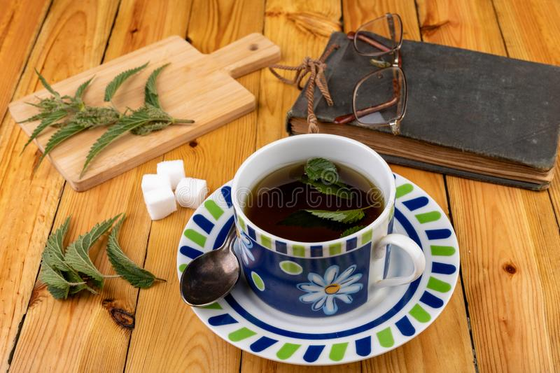 Tasty nettle tea in a cup. Freshly cut nettle and infected tea on a wooden table. Light background glass alternative beauty beverage breakfast care color diet stock photo