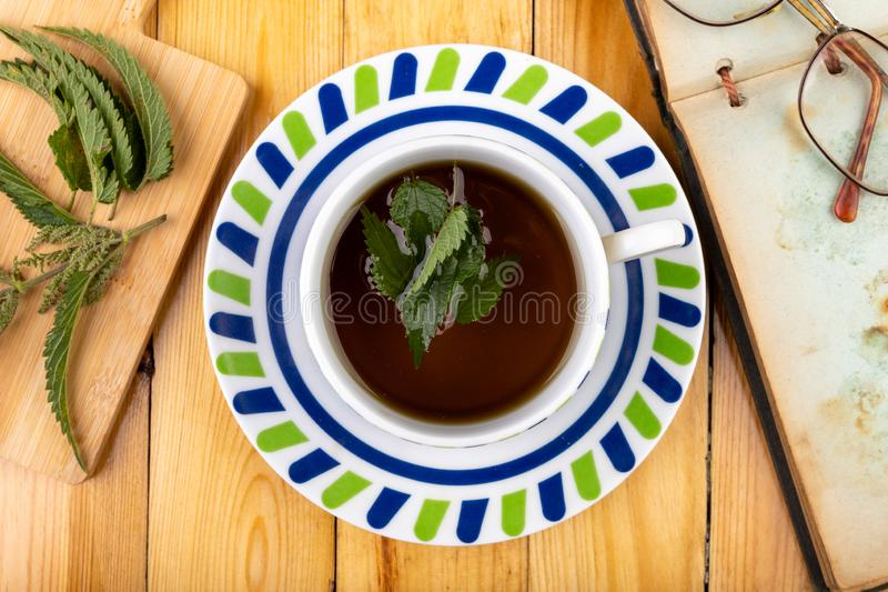 Tasty nettle tea in a cup. Freshly cut nettle and infected tea on a wooden table. Light background glass alternative beauty beverage breakfast care color diet stock image
