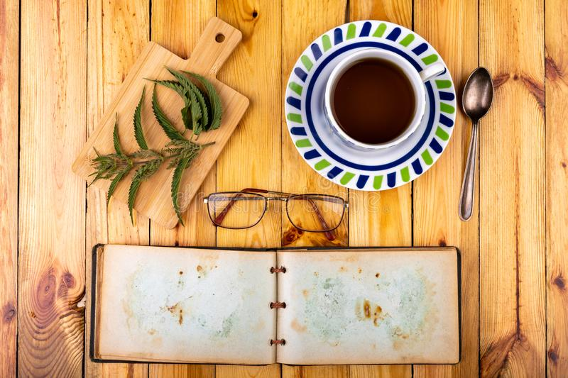 Tasty nettle tea in a cup. Freshly cut nettle and infected tea on a wooden table. Light background glass alternative beauty beverage breakfast care color diet royalty free stock photos