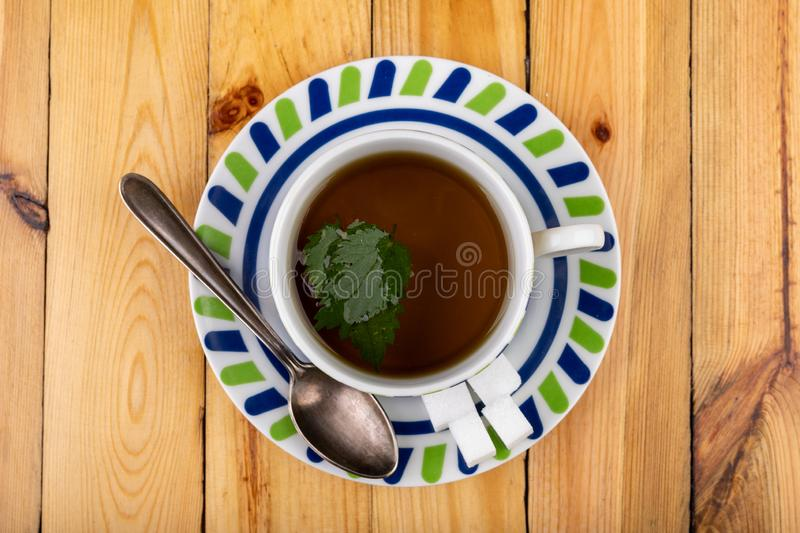 Tasty nettle tea in a cup. Freshly cut nettle and infected tea on a wooden table. Light background glass alternative beauty beverage breakfast care color diet royalty free stock image