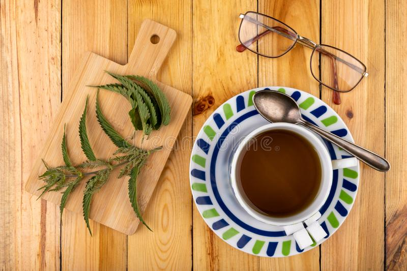 Tasty nettle tea in a cup. Freshly cut nettle and infected tea on a wooden table. Light background glass alternative beauty beverage breakfast care color diet royalty free stock images