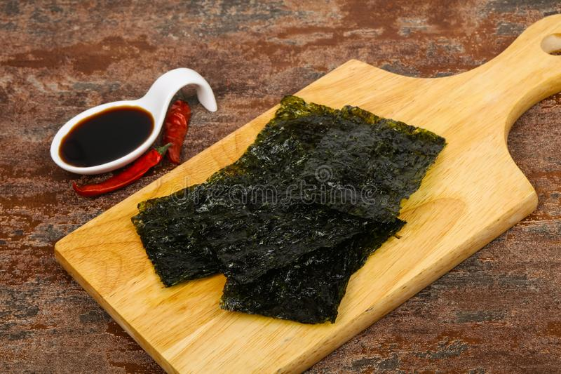 Tasty Nori chips. With soya sauce royalty free stock photography