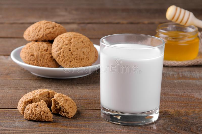 Tasty oatmeal cookies with honey and milk on a napkin on a brown wooden table stock photography