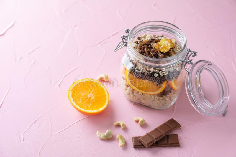 Tasty oatmeal dessert with fresh orange and chocolate in glass jar on color textured background royalty free stock image