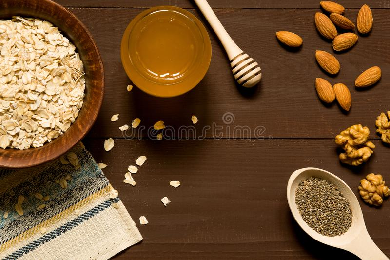 Oatmeal with nuts in bowl on brown background royalty free stock image