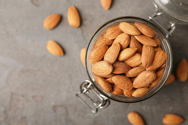 Tasty organic almond nuts in jar and space for text on table royalty free stock photography