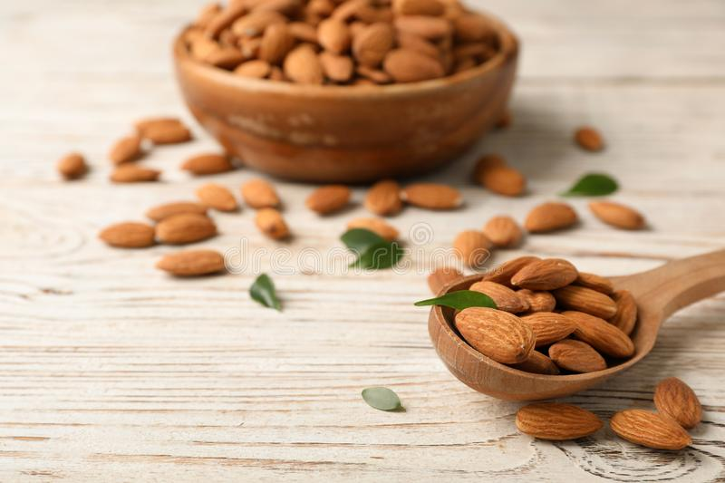Tasty organic almond nuts in spoon on table stock images
