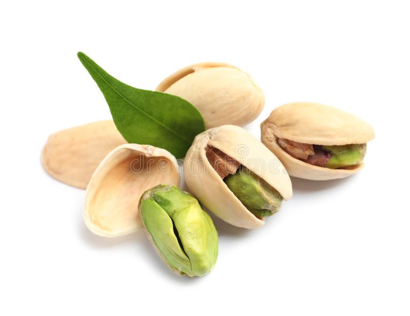 Tasty organic pistachio nuts and leaf on white background, closeup stock photography