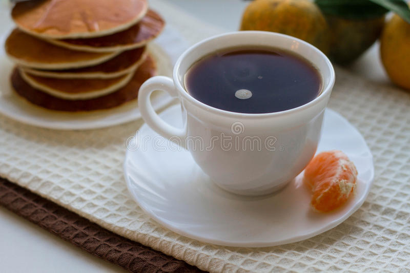 Tasty pancakes with a cup of coffee on a white table stock images