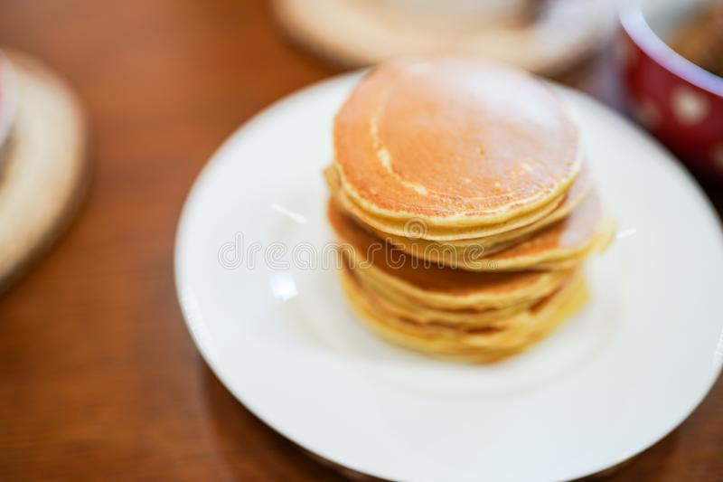 Tasty pancakes on the plate on wooden table. cooking in the kitchen royalty free stock photos