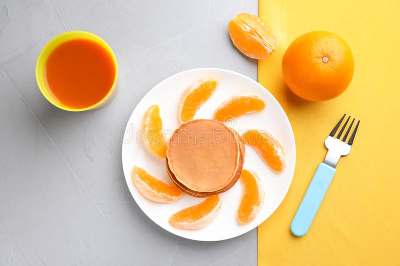 Tasty pancakes served with orange and juice on table, flat lay. Creative idea for kids breakfast royalty free stock image