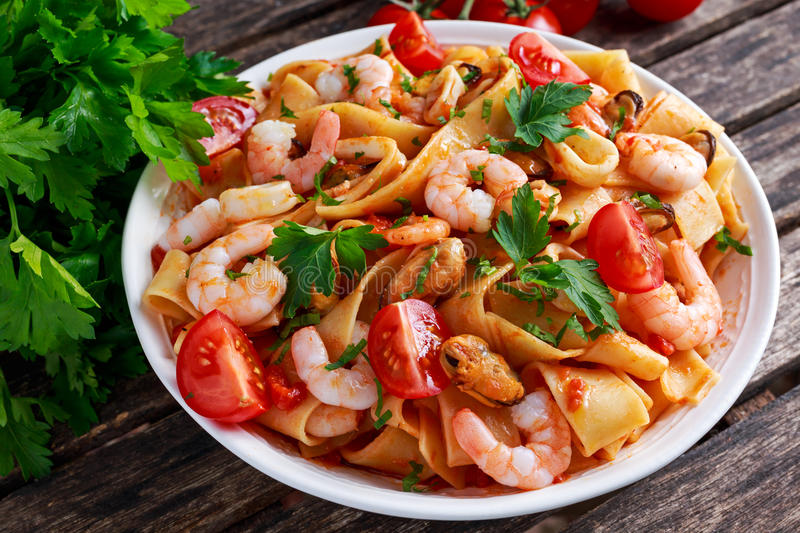 Tasty Pappardelle pasta with shrimp, Squid, mussel, tomatoes and herbs. Tasty Pappardelle pasta with shrimp, Squid, mussel, tomatoes and herbs stock image