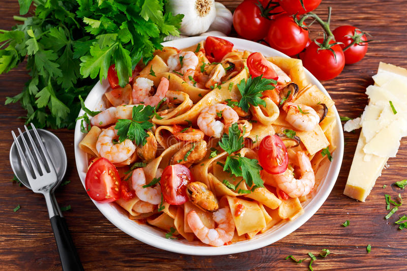 Tasty Pappardelle pasta with shrimp, Squid, mussel, tomatoes and herbs. Tasty Pappardelle pasta with shrimp, Squid, mussel, tomatoes and herbs stock photos