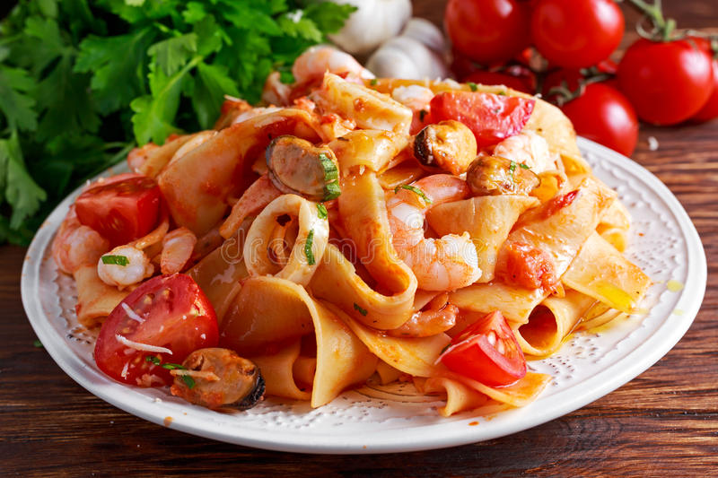 Tasty Pappardelle pasta with shrimp, Squid, mussel, tomatoes and herbs. Tasty Pappardelle pasta with shrimp, Squid, mussel, tomatoes and herbs royalty free stock photos