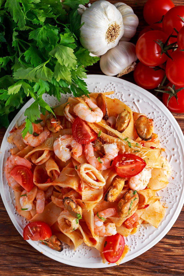 Tasty Pappardelle pasta with shrimp, Squid, mussel, tomatoes and herbs. Tasty Pappardelle pasta with shrimp, Squid, mussel, tomatoes and herbs stock photo
