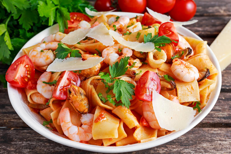 Tasty Pappardelle pasta with shrimp, Squid, mussel, tomatoes and herbs. Tasty Pappardelle pasta with shrimp, Squid, mussel, tomatoes and herbs royalty free stock images