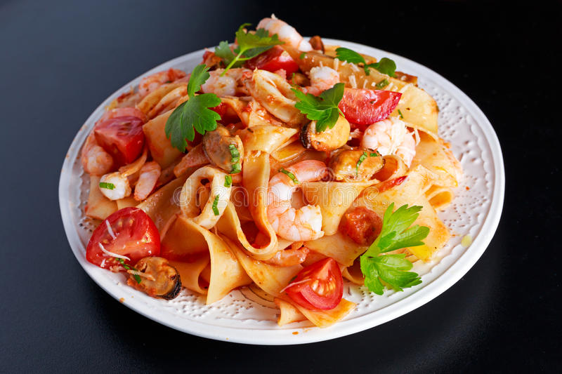 Tasty Pappardelle pasta with shrimp, Squid, mussel, tomatoes and herbs. Tasty Pappardelle pasta with shrimp, Squid, mussel, tomatoes and herbs royalty free stock photography
