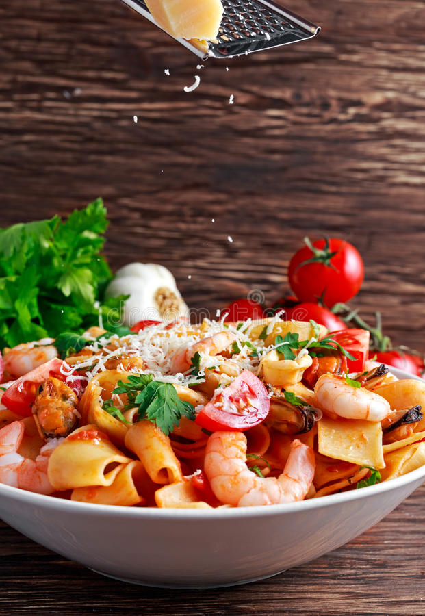 Tasty Pappardelle pasta with shrimp, Squid, mussel, tomatoes and herbs. parmesan cheese on top. selected focus.  stock images