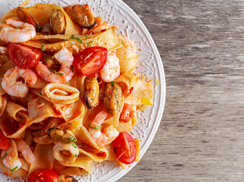 Tasty Pappardelle pasta with shrimp, Squid, mussel, tomatoes on wooden table.  stock photos